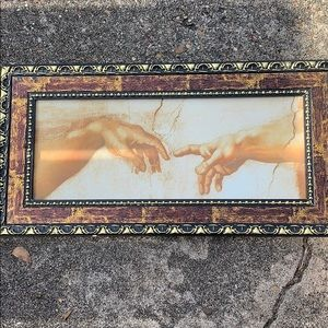 Two hands touching framed art